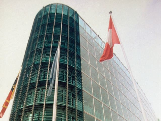 Ein grosses Glasgebäude mit einer Schweizer Fahne davor.