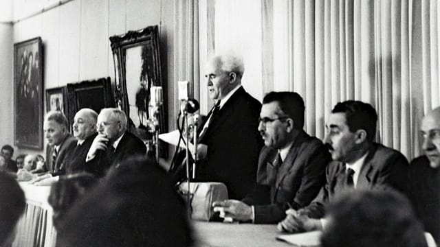 Gurion liest vor, am Tisch sitzen Männer.