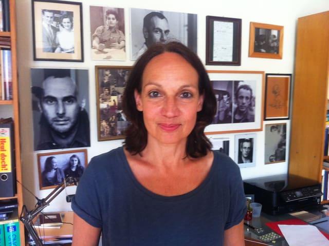 Mation Brasch in ihrem Arbeitszimmer. Im Hintergrund hängen Schwarz-Weiss-Fotos von verschiedenen Personen.