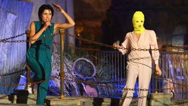 Tolokonnikowa auf einer Bühne, neben ihr eine andere Frau mit einer bunten, gestrickten Maske.