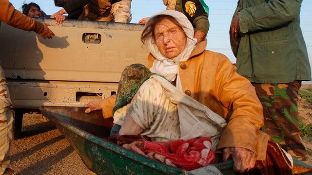 Eine ältere Frau sitzt in einer Schubkarre