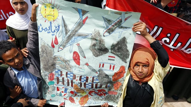 Kinder halten eine Zeichnung in die Luft.