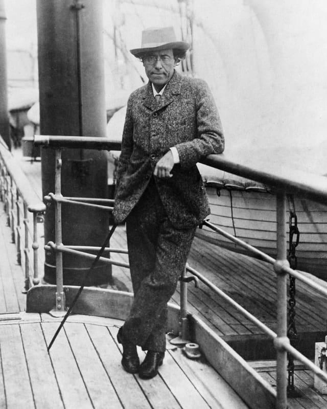 Altes Schwarzweissfoto: MAn nmit Hut und Stock an Bord eines Schiffes