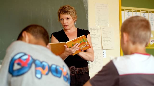 Eine Lehrerin steht vor einer Schulklasse.