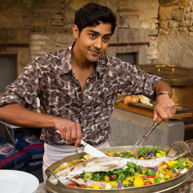 Indischer Koch schneidet Fisch in einem Paella-Kochtopf