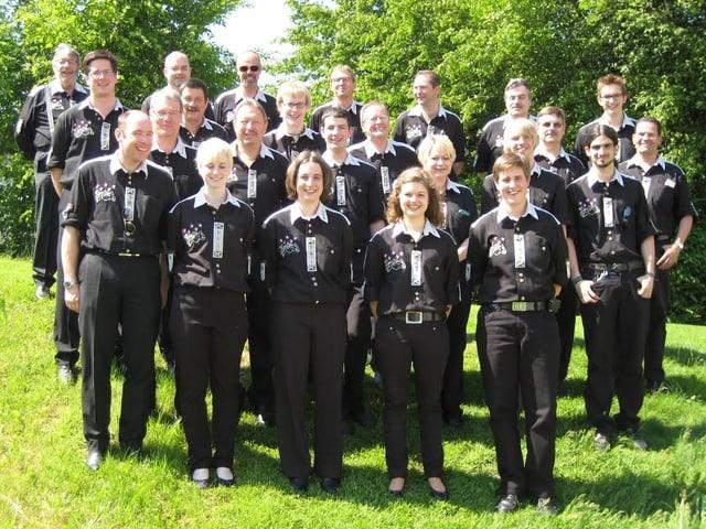 Die Blasmusikanten und -musikantinnen tragen schwarze Hemden und Hosen und posieren fürs Gruppenbild auf einer grünen Wiese.