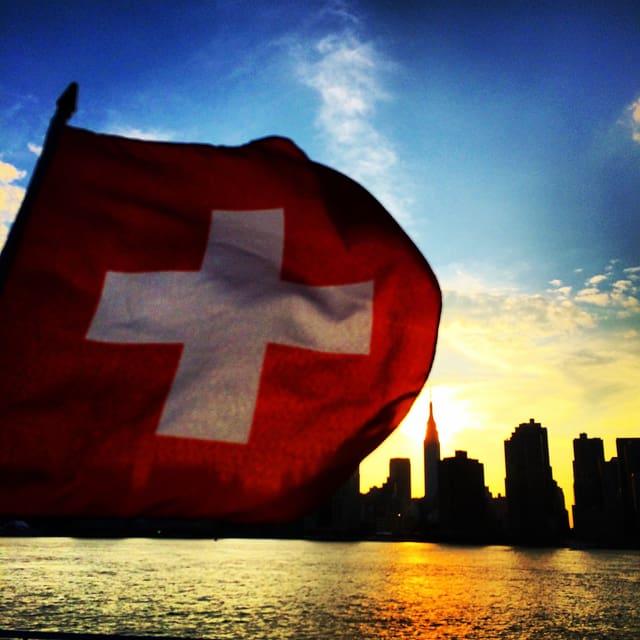 Die Schweizer Flagge vor der Manhattan skyline (rechts das Empire State Building)