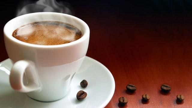 Weisse Tasse mit rauchendem Kaffee. Daneben lieben einzelne Kaffeebohnen