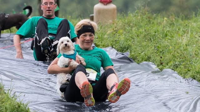 Eine Hundehalterin hält ihren kleinen Hund fest und rutscht auf einer Plastikplane den Hang herunter.