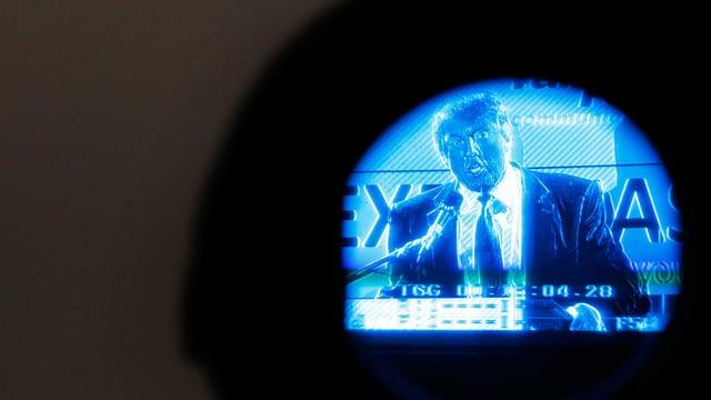 Runder Ausschnitt eines Negativ-Bildes: Donald Trump steht vor einem Mikrofon.