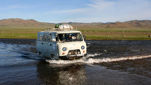 Ein alter Bus fahrt in einem Fluss, den Bus sieht man schräg von vorne, am Steuer sitzt ein Mann. Auf dem Dach, sowie im Inneren des Busses hat es Waren. Im Hintergrund sieht man eine weite Hügellandschaft, wie es sie in Kirgistan gibt.