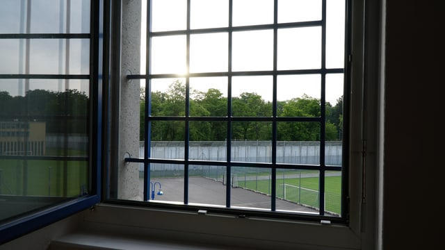 Blick durch ein vergittertes Fenster. Zu sehen ist ein Fussballplatz, dahinter eine Mauer und ein Wald. Die Sonne scheint.
