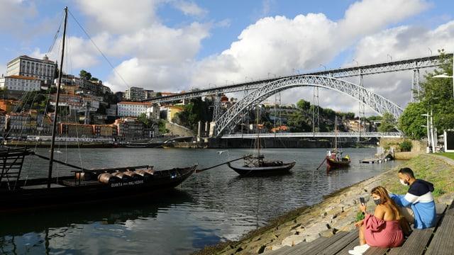 Paar am Ufer eines Flusses. Dahinter die Brücke von Porto.