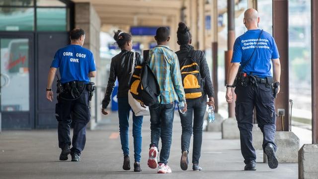Zwei Polizisten begleiten drei dunkelhäutige Jugendliche