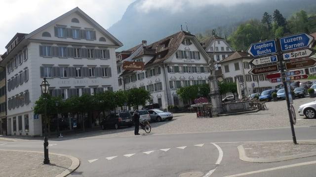 Dorfplatz von Stans mit Verkehrsschildern, Autos und Velofahrern.