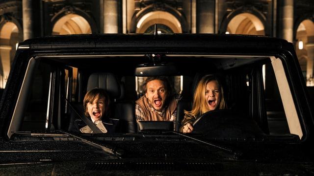 Ein Auto von vorn. Am Steuer sitzt ein Mädchen, auf dem Beifahrersitz ebenfalls ein Kind. In der Mitte hinten sietzt ein Erwachsener. Alle drei haben die Gesichter zu einem Schrei verzogen.