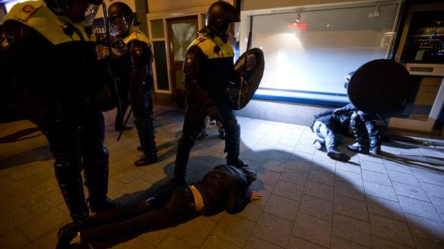 Polizisten stehen bei Personen, die auf dem Trottoir liegen.
