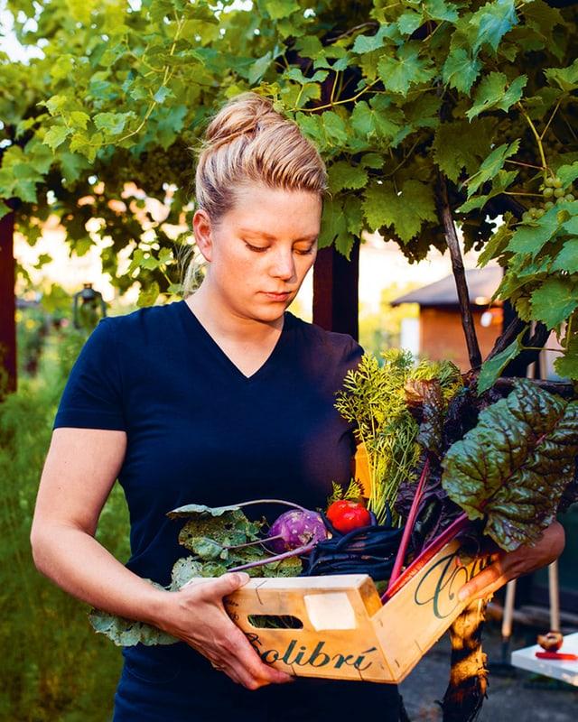 Eine junge Frau steht in einem grünen Garten und hat einen Korb in der Hand voller verschiedener Gemüse.
