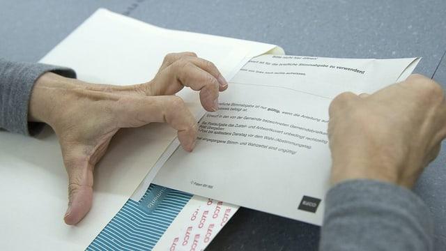Eine Person steckt einen Stimmzettel in ein Wahlcouvert.