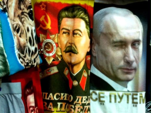 T-Shirt-Auslage an einem Kiosk: links Putin-MOtiv auf rotem Hintergund, rechts Putin.