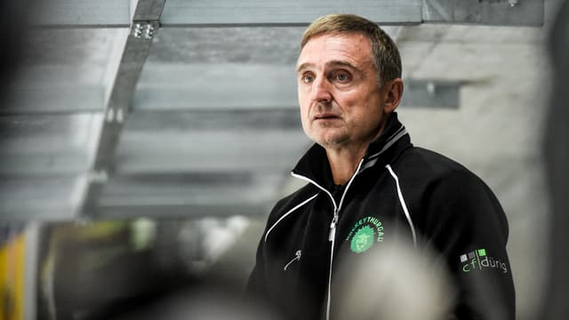 Trainer Christian Weber steht mit schwarzer Vereinsjacke mit grünem Emblem an der Seitenwand des Eisfelds.