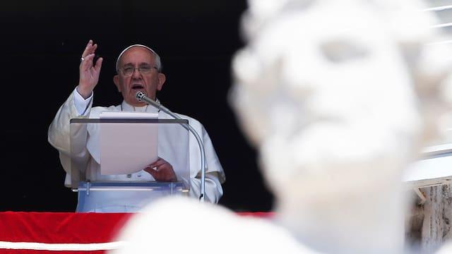 Papst an einem Rednerpult. Im Vordergrund eine antike Statue.