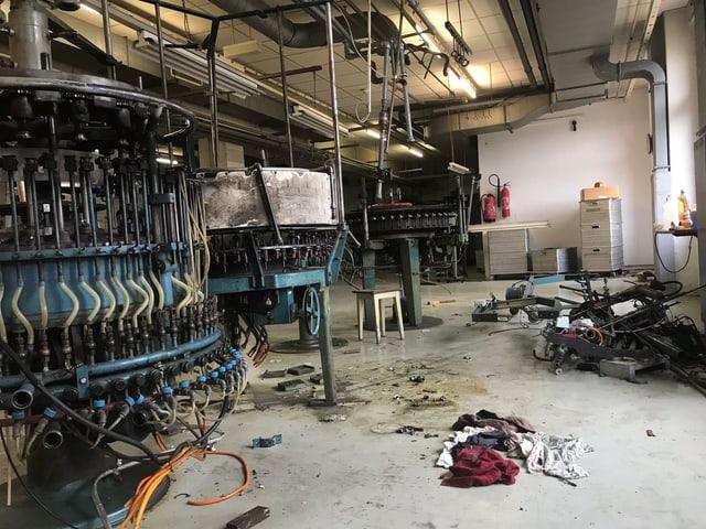 Alte museumsreife Maschinen in einer halbleeren Fabrikhalle.