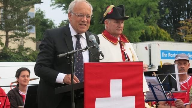 Bundesrat Johann Schneider-Ammann steht an einem Rednerpult mit einer Schweizer Fahne, rechts von ihm der Bundesweibel.