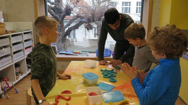 """Drei Kinder und der Jugendliche an einem Tisch, auf dem die Kinder mit Knete Zahlen """"schreiben""""."""