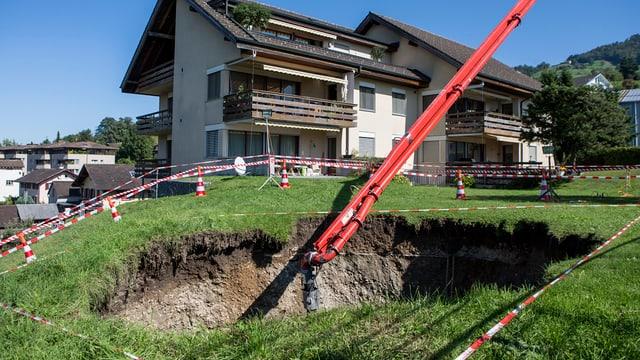 Ein grosses Loch klafft in einer grünen Wiese vor einem Wohnhaus.