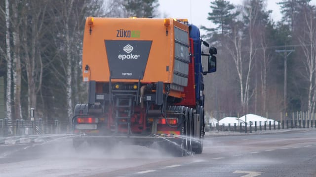 Ein Lastwagen, der gerade Sole auf eine Fahrbahn spritzt.
