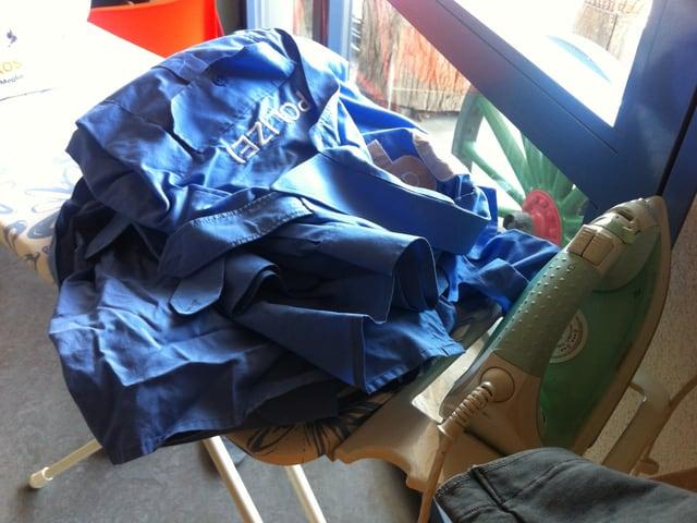 Ein Bügelbrett mit Bügeleisen und Polizekleidung.