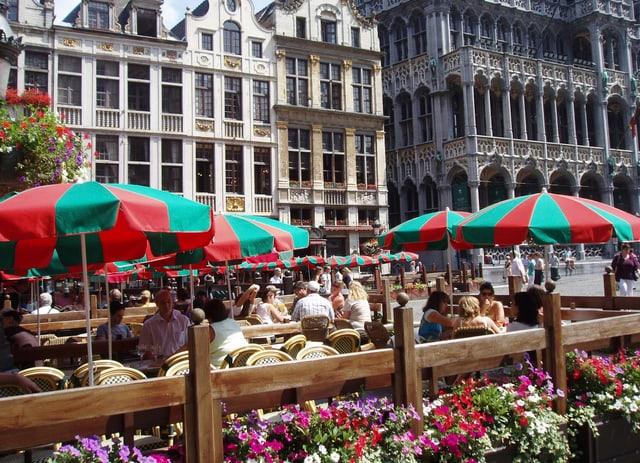 Menschen sitzen auf einem beschaulichen Platz in der Stadt Brüssel beisammen.