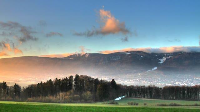 Rote Wolken bei Sonnenuntergang über einem Bergkamm, davor Wiese und Wald.
