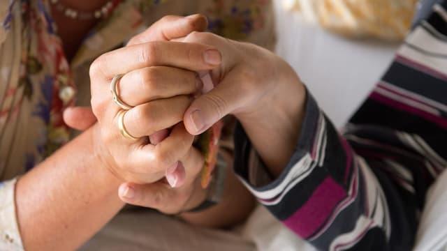 Symbolbild für Sterbehilfe. Älteres Paar hält Hände auf dem Sterbebett.