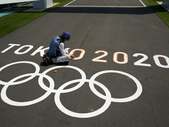 Person pinselt Logo der Olympischen Spiele in Tokio auf den Asphalt