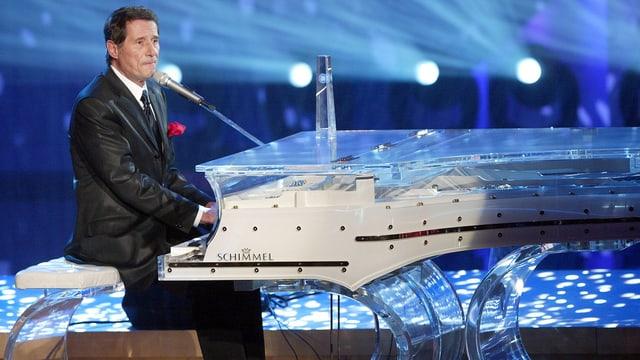 Der Musiker Udo Jürgens sitzt an einem durchsichtigen Klavier auf der Bühne.