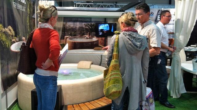 Zwei Frauen und ein Mann stehen vor einem Whirlpool.