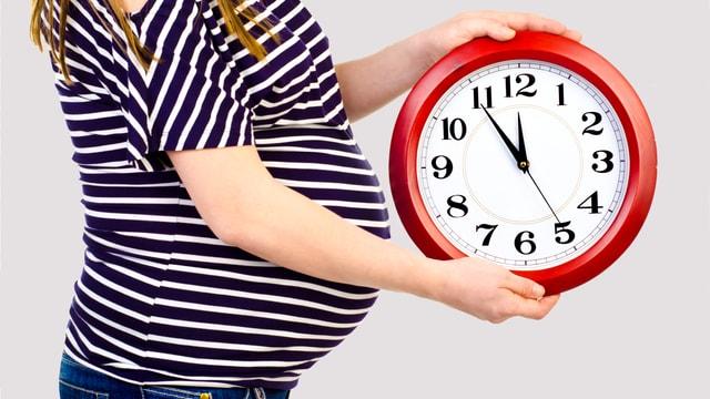 Eine hochschwangere Frau hält eine Uhr, die fünf vor zwölf anzeigt.