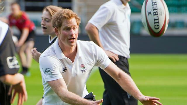 Prinz Harry fängt einen Rugbyball.