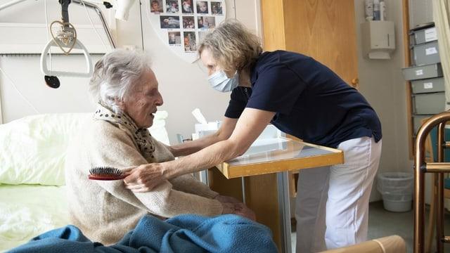 Pflegefachfrau betreut eine alte Frau