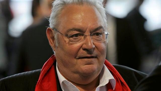 Mathias Gnädinger im Anzug mit rotem Halstuch.