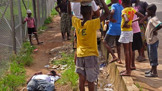 Kinder beobachten liegenden Mann auf der Strasse