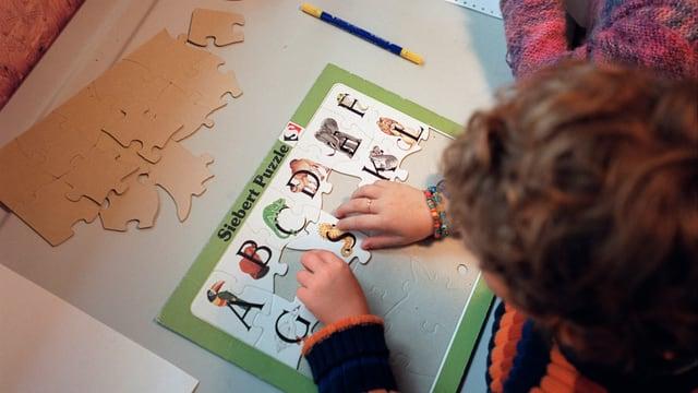 Einf Kind lernt das ABC mithilfe eines Puzzles.
