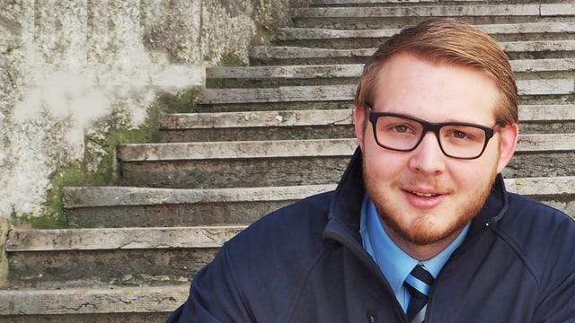 Der junge Sänger trägt eine blaues Hemd mit Krawatte und einer dunkelblauen Jacke und sitzt auf einer Steintreppe.