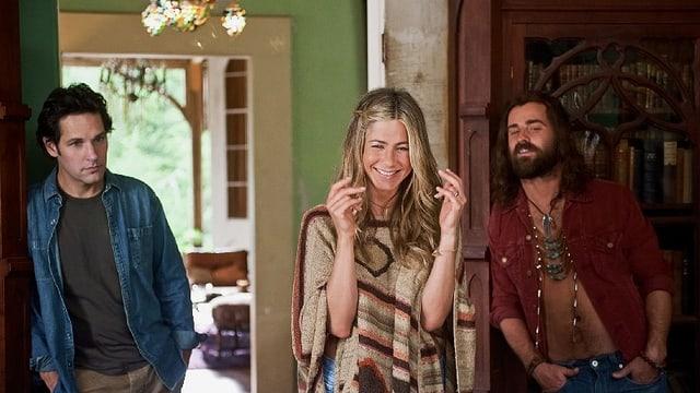 Links steht ein Mann in Jeanshemd und ernstem Blick. In der Mitte eine lachende Frau in Hippiekleidung. Rechts ein bärtiger Mann mit langem Haar und aufgeknöpftem Hemd und Hippieschmuck.