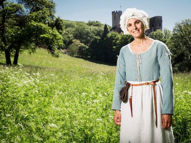 Frau in mittelalterlicher Kleidung auf einer Wiese mit einer Burg im Hintergrund