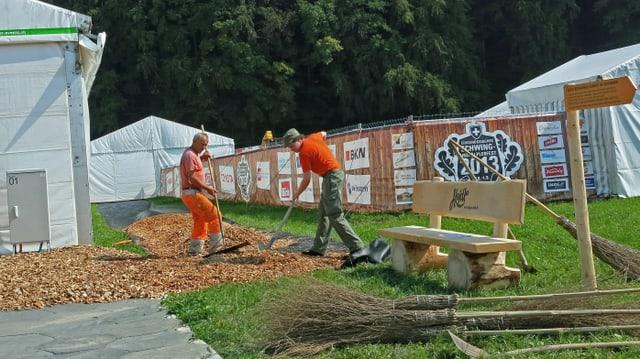 Zwei Arbeiter verteilen Holzschnitzel für einen Gehweg.