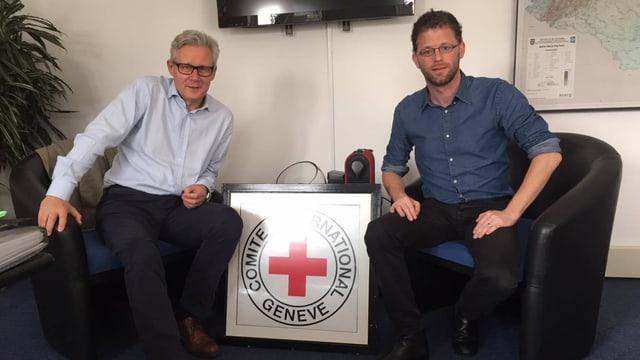 Zwei Männer sitzen nebeneinander, dazwischen ein IKRK-Emblemschild.