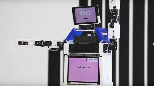 Ein Roboter hebt die Arme hoch. Eine Gruppe Rentner macht es ihm nach.